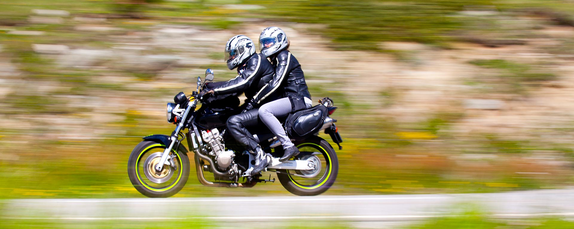a couple riding a black motorbike at high speed