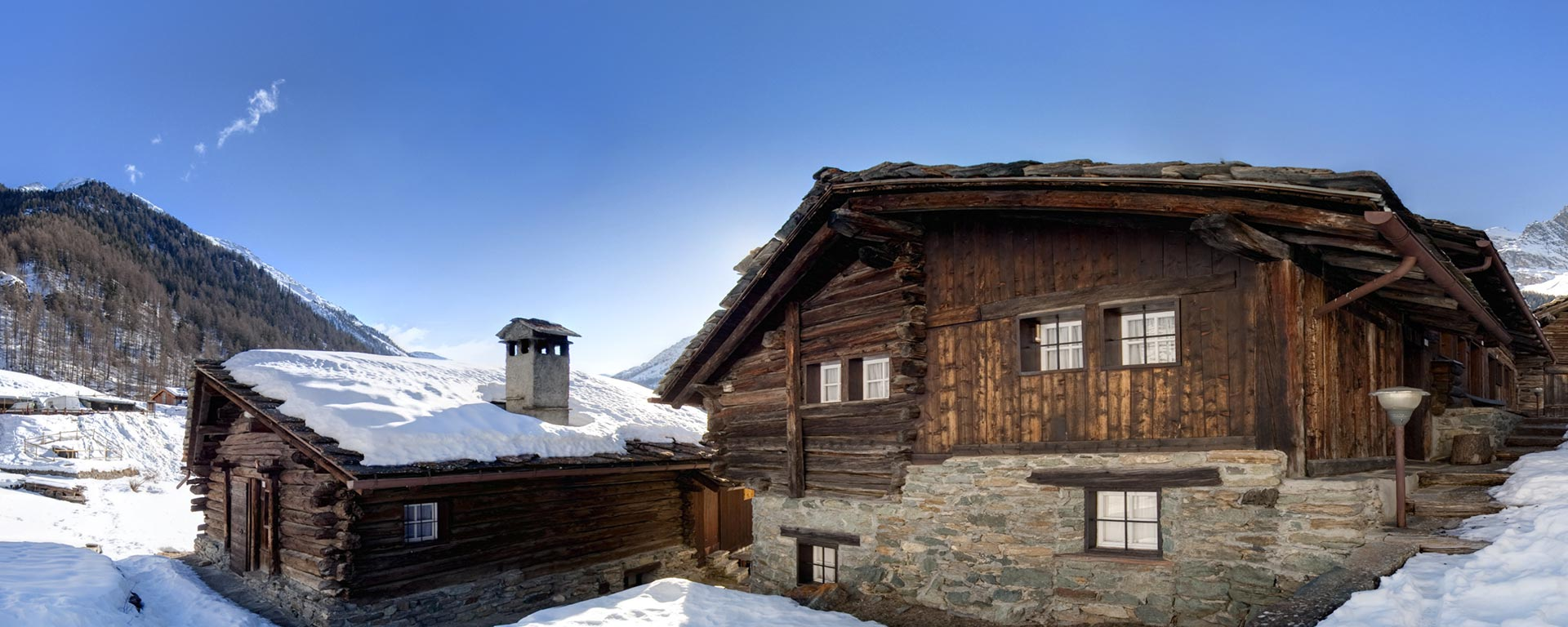two snow covered mountain huts in the Dolomites near San Vigilio di Marebbe during a sunny winter day