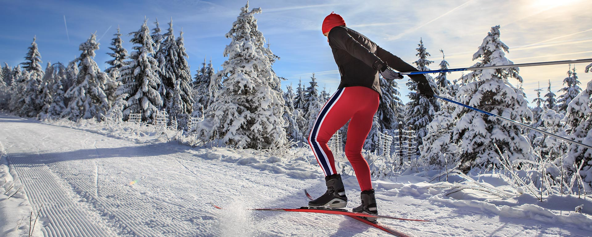 a man dressed in red and black is cross country skiing in the Dolomites