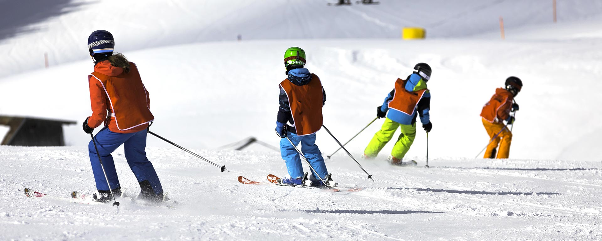 some kids with orange vests during a ski course organised by a ski school