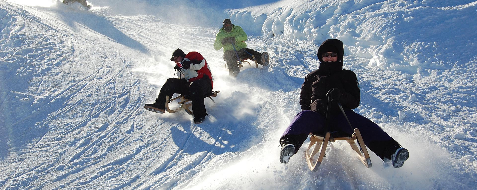 a family is having fun on their sleds on a slope in South Tyrol